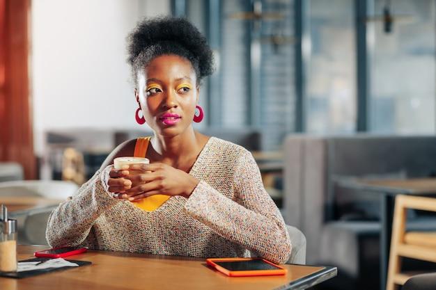 Ciesząc się kawą młoda, inteligentna piękna freelancerka ciesząca się kawą w przytulnej kafeterii