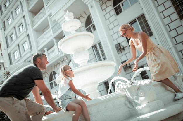 Ciesząc się latem. entuzjastyczna dziewczynka siedzi z rodzicami na fontannie i ochlapuje ich wodą.