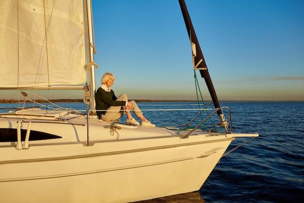 Ciesząc się luksusowym życiem piękna starsza kobieta siedząca na boku pływającej żaglówki lub pokładu jachtu
