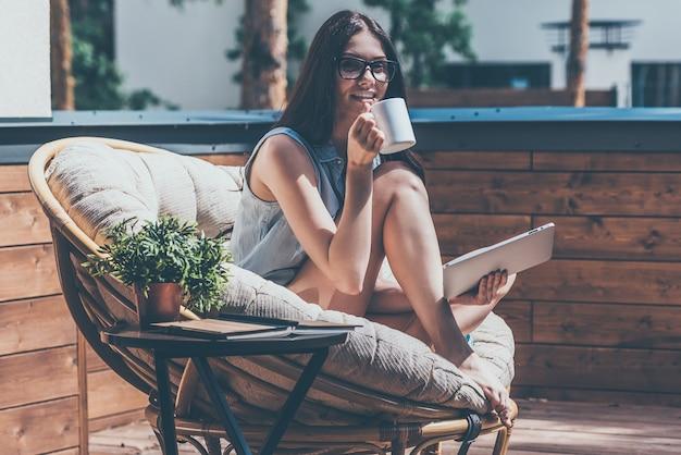 Ciesząc się poranną kawą. piękna młoda uśmiechnięta kobieta trzymająca filiżankę kawy i patrząca w kamerę siedząc w dużym wygodnym krześle na jej tarasie na świeżym powietrzu
