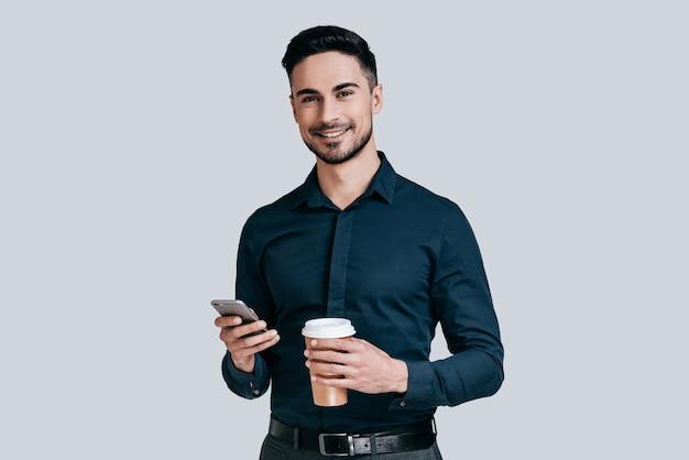 Ciesząc się przerwą na kawę. przystojny młody mężczyzna trzymający jednorazowy kubek i patrzący na kamerę