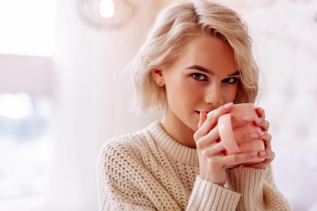 Ciesząc się smaczną herbatą. zbliżenie młodej pięknej kobiety z bobem, cieszącej się smaczną herbatą w sypialni