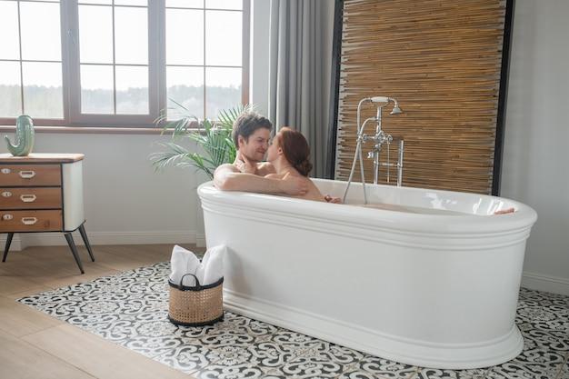 Ciesząc się sobą. mężczyzna i kobieta wspólnie kąpią się i wyglądają na zadowolonych