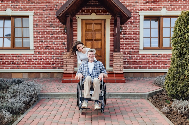 Ciesząc się w rodzinnym czasie starszym mężczyzną na wózku inwalidzkim i uśmiechniętą córką w ogrodzie