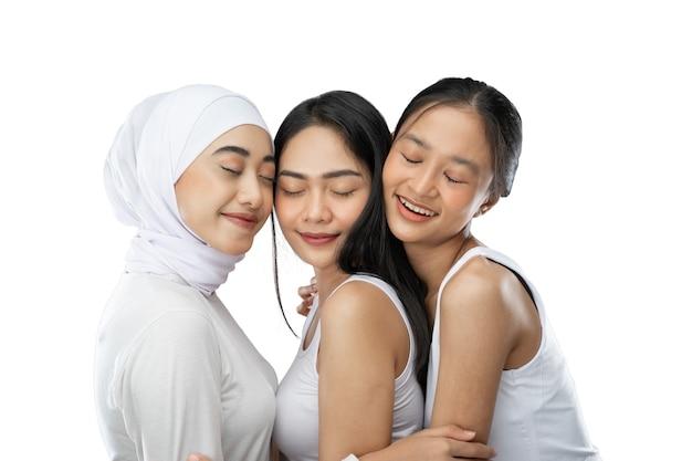 Ciesząc się zawoalowaną dziewczyną i dwie młode azjatki przytulające się z zamkniętymi oczami