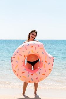 Ciesząca się opalenizną. piękna szalona kobieta relaksuje i bawi się nadmuchiwanym pierścieniem na plaży. letnie wakacje i koncepcja wakacji.