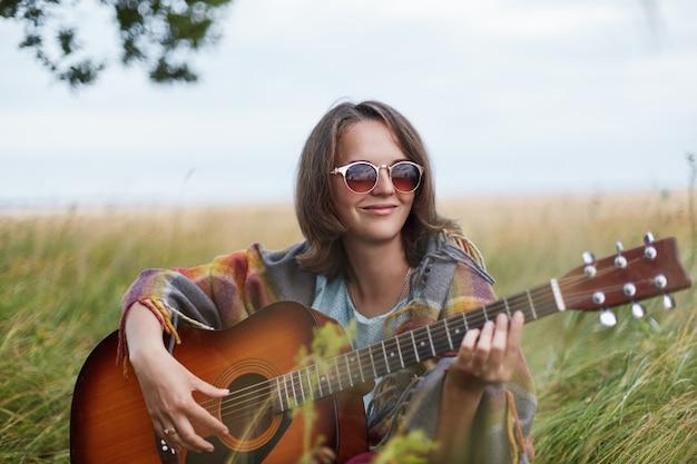 Ciesząca się, że kobieta jest sama z naturą, grając na gitarze, pamiętając przyjemne chwile z życia. ładna młoda kobieta jest ubranym okulary przeciwsłonecznych siedzi przy greenland