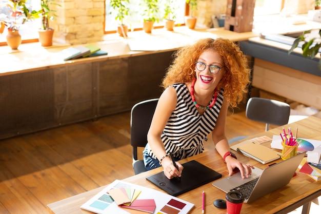 Cieszący dzień pracy. wesoła rudowłosa menedżerka kreatywna czuje się naprawdę szczęśliwa, ciesząc się dniem pracy