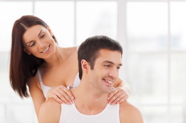 Cieszący masaż. piękna młoda kochająca się para siedzi razem w łóżku, podczas gdy kobieta robi masaż dla swojego chłopaka