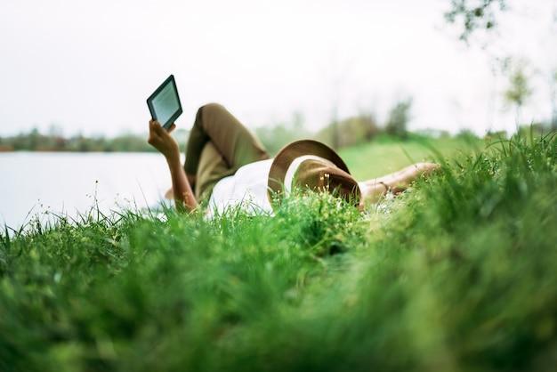Cieszący się e-book w pobliżu jeziora. dziewczyna leży na trawie.