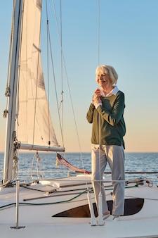 Cieszący się niesamowitym widokiem pionowego ujęcia szczęśliwej starszej kobiety stojącej na pokładzie żaglówki lub jachtu