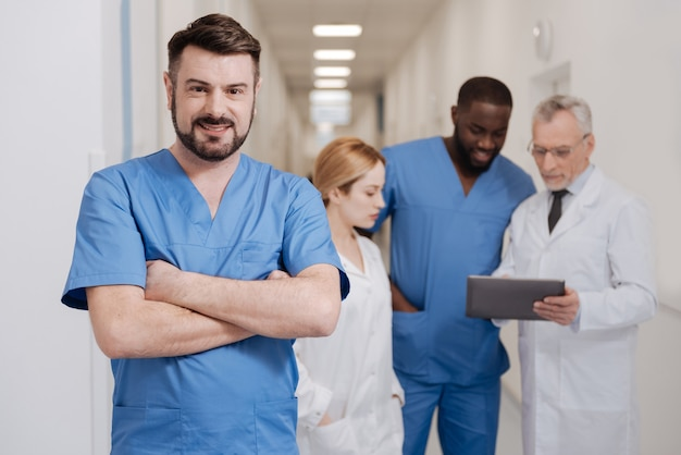 Cieszący się pracą w przyjaznym zespole. charyzmatyczny wykwalifikowany brodaty lekarz pracujący w klinice ze skrzyżowanymi rękami, podczas gdy inni koledzy testują gadżet w tle