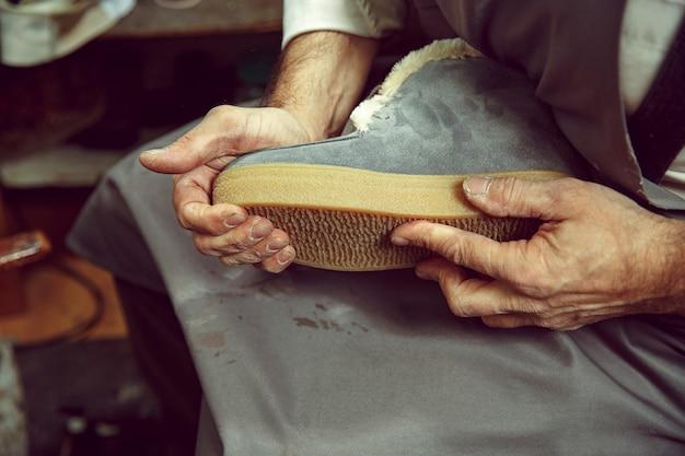 Cieszący się procesem tworzenia butów na zamówienie. miejsce pracy projektanta obuwia. ręce szewca zajmującego się narzędziem szewc, z bliska