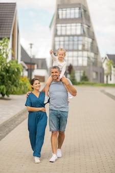 Cieszący wieczorny spacer. szczęśliwa wesoła rodzina czuje się dobrze, ciesząc się wieczornym spacerem w wiejskim miasteczku