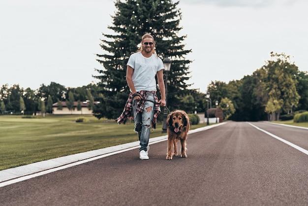 Cieszę się miłym dniem. pełna długość przystojnego młodego mężczyzny spacerującego z psem podczas spędzania czasu na świeżym powietrzu