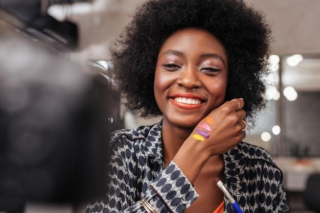 Cieszę się pracą. śliczna kobieta z kręconymi włosami pokazująca nowe kolory podczas pracy w akademii mody