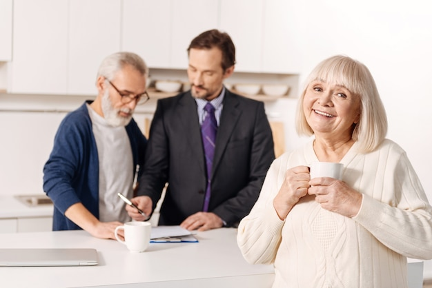 Cieszę się użyteczną obsługą. urocza zadowolona wesoła starsza kobieta stojąca i relaksująca się, podczas gdy jej mąż podpisuje dokumenty z prawnikiem