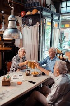 Cieszę się wieczorem. trzej emerytowani mężczyźni cieszą się wieczorem przy wspólnym piwie