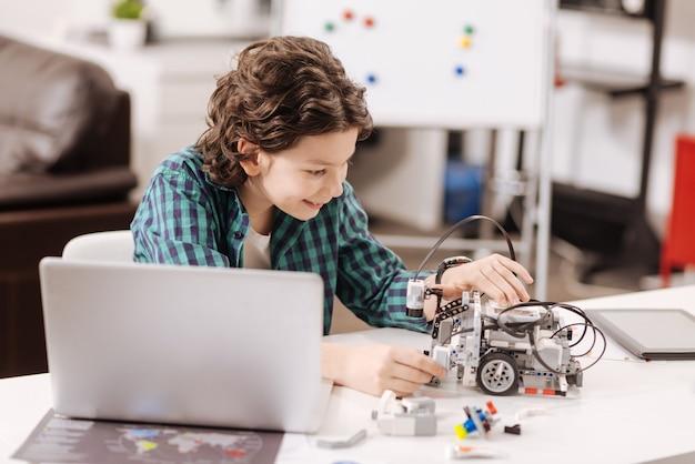 Cieszę się wolnym czasem. uśmiechający się uroczy, wykwalifikowany dzieciak siedzi w klasie przedmiotów ścisłych i używa urządzeń podczas nauki i wyrażania szczęścia