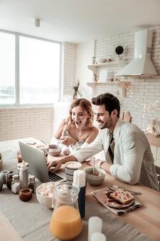 Cieszę się z filmu. brodaty przystojny mężczyzna i jego śliczna długowłosa żona wyglądają na rozbawionych podczas oglądania filmu na laptopie