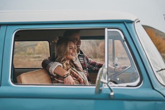 Cieszę się z podróży samochodowej. piękna młoda para obejmując i uśmiechając się, siedząc w niebieskim mini van w stylu retro