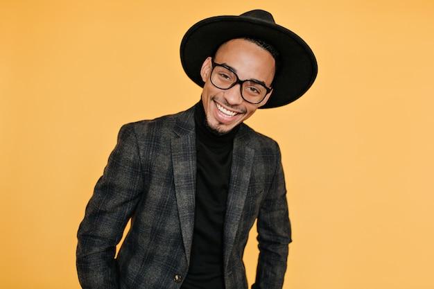 Cieszę się, że afrykański mężczyzna w czarnej koszuli i szarej kurtce pozuje. zdjęcie pozytywnego faceta mulat ze szczerym uśmiechem na białym tle na pomarańczowej ścianie.