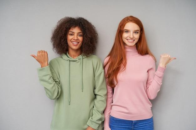 Cieszę się, że atrakcyjne młode panie ubrane w stroje codzienne pokazują kciuki w różnych kierunkach i patrzą wesoło z pozytywnym uśmiechem, odizolowane na szarej ścianie