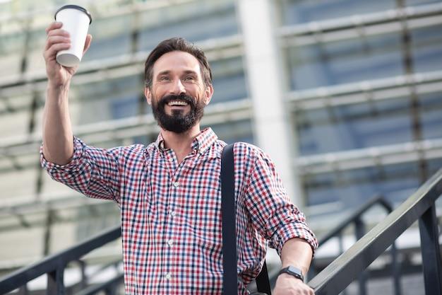 Cieszę się że cię widzę. pozytywny dorosły człowiek pije kawę witając przechodnia na zewnątrz