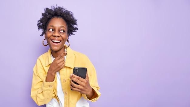 Cieszę się, że ciemnoskóra, kędzierzawa kobieta uśmiecha się szeroko, ma optymistyczny nastrój, używa telefonu komórkowego do wysyłania wiadomości tekstowych