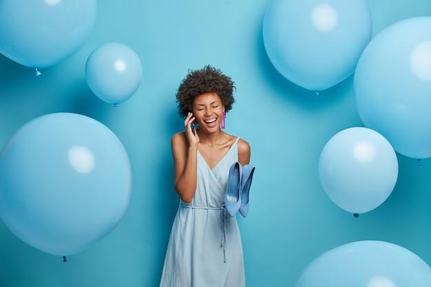 Cieszę się, że ciemnoskóra młoda kobieta rozmawia przez telefon, pozytywnie się śmieje, ubrana w stylową sukienkę i buty