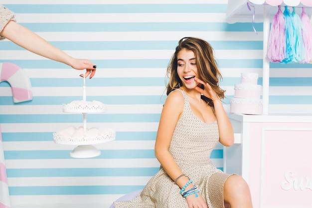 Cieszę się, że dziewczyna patrzy na pyszne ciasta i zamierza je zjeść. portret kuszącej młodej kobiety w eleganckiej sukience, cieszącej się słodkim smakiem ptasie mleczko i uśmiechnięta, siedząca na pasiastej ścianie.