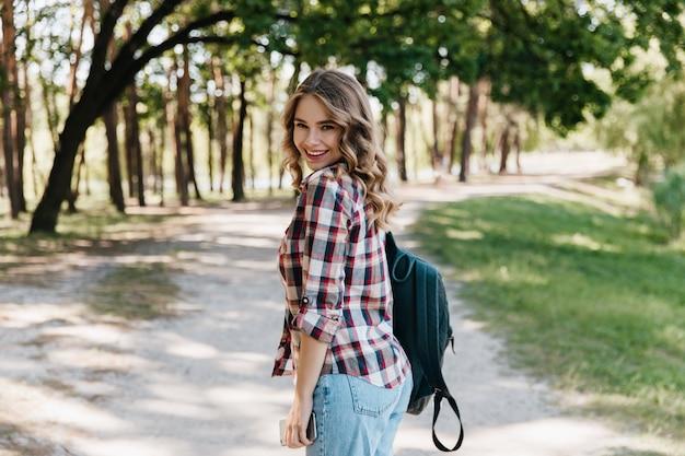 Cieszę się, że dziewczyna w kraciaste koszule i niebieskie dżinsy stoi w parku. zainspirowana kobieta ze skórzanym plecakiem uśmiechnięta w wiosenny dzień.