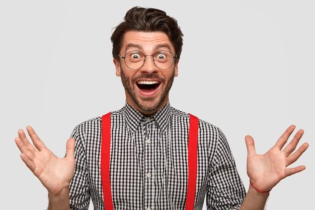 Cieszę się, że hipster uściska starego przyjaciela, cieszy się ze spotkania, ma zachwycony wyraz twarzy, elegancko ubrany