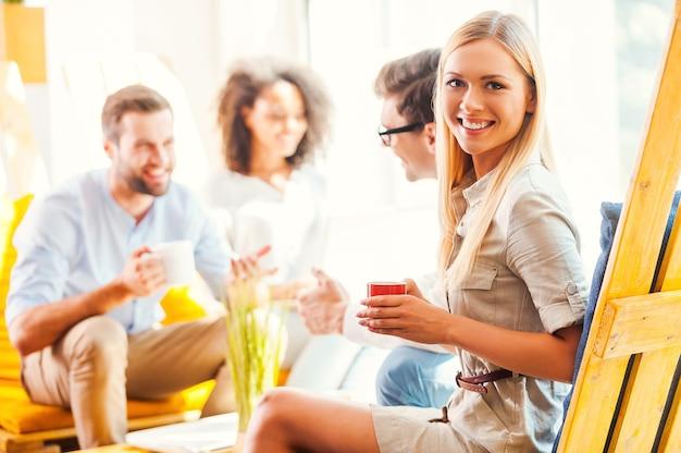 Cieszę się, że jestem częścią odnoszącego sukcesy zespołu. szczęśliwa młoda kobieta trzymająca filiżankę kawy i patrząca w kamerę, podczas gdy jej koledzy dyskutują o czymś w tle