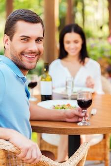 Cieszę się, że jestem z nią. piękna młoda para relaksuje się razem w restauracji na świeżym powietrzu, podczas gdy mężczyzna patrzy na kamerę i uśmiecha się
