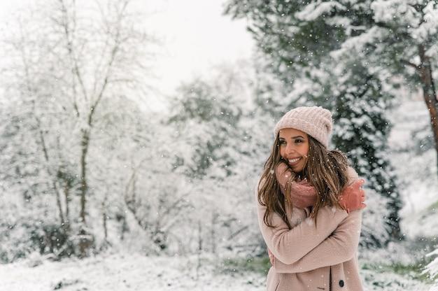 Cieszę się, że kobieta w ciepłych ubraniach stoi w zaśnieżonym lesie i odwraca wzrok, ciesząc się zimowym weekendem