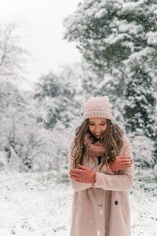 Cieszę się, że kobieta w ciepłych ubraniach stoi w zaśnieżonym lesie i spogląda w dół, ciesząc się zimowym weekendem