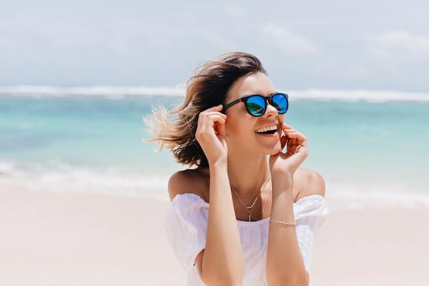 Cieszę się, że ładna kobieta w błyszczących okularach przeciwsłonecznych wyrażająca szczęście w ośrodku. plenerowe ujęcie wesołej pięknej pani pozującej na morzu w wietrzny dzień.
