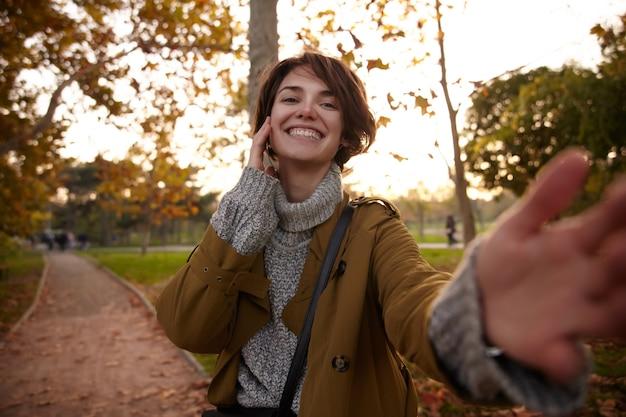 Cieszę się, że młoda atrakcyjna brunetka kobieta z przypadkową fryzurą ubrana w modną ciepłą odzież, szlifująca alejkę w parku i uśmiechająca się wesoło z uniesioną ręką