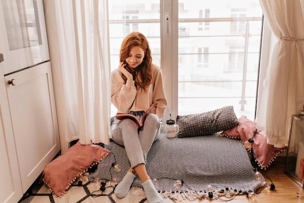 Cieszę się, że młoda dama siedzi w swoim przytulnym pokoju. urocza imbirowa dziewczyna pozuje z książką.