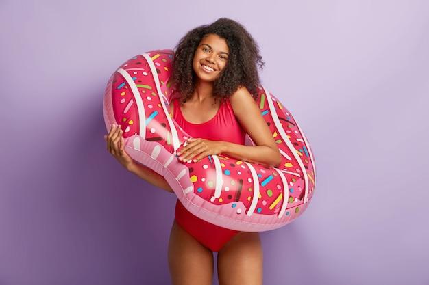 Cieszę się, że młoda kobieta z kręconymi włosami pozuje z pływającym basenem