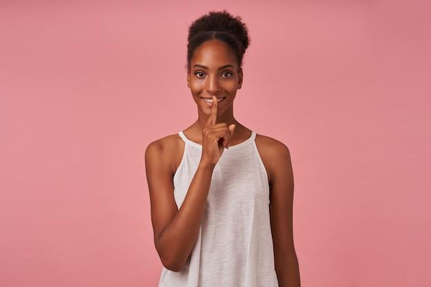 Cieszę się, że młoda, ładnie kręcona kobieta z fryzurą kok, trzymając palec wskazujący na ustach, patrząc wesoło z przodu, stojąc nad różową ścianą