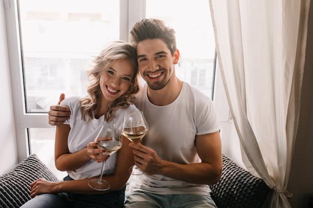 Cieszę się, że młody człowiek obchodzi rocznicę z żoną. uśmiechnięta dziewczyna korzystających z szampana.