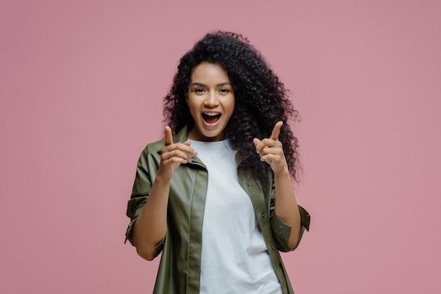 Cieszę się, że pewna siebie kobieta z afro włosami wskazuje palcami do przodu
