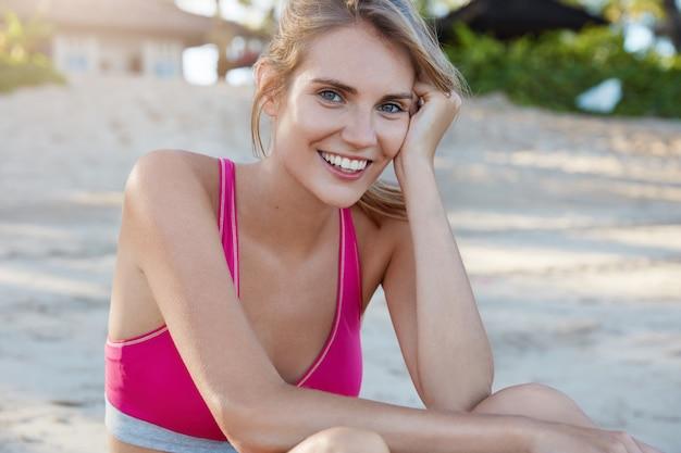 Cieszę się, że piękna suczka odpoczywa po treningu fizycznym, nosi różowy sportowy stanik, ma wesoły wyraz, siedzi na piaszczystej plaży, ma zadowoloną minę. ludzie, aktywny tryb życia i koncepcja motywacji.