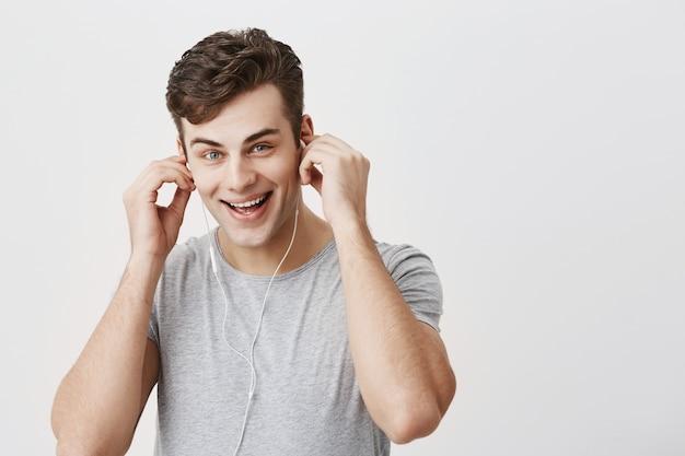 Cieszę się, że pozytywny kaukaski mężczyzna uśmiecha się radośnie, słucha muzyki w słuchawkach, trzyma ręce za uszami, lubi ulubione piosenki, używa aplikacji muzycznej. młody europejski mężczyzna lubi przyjemne melodie