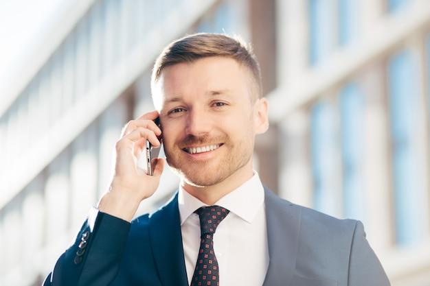Cieszę się, że przystojny wesoły mężczyzna przedsiębiorca nosi formalny garnitur, krawat i białą koszulę, trzyma nowoczesny telefon komórkowy