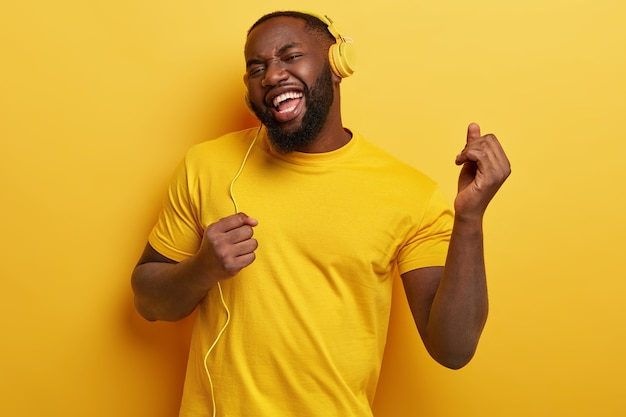 Cieszę się, że pulchny ciemnoskóry mężczyzna tańczy, porusza się do muzyki, ma nowoczesne słuchawki stereo, uśmiecha się pozytywnie, jest w duchu. całość w kolorze żółtym. beztroski facet słucha skocznej muzyki