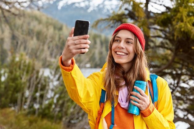 Cieszę się, że śliczna ciemnowłosa dziewczyna robi selfie portret na telefon komórkowy, ubrana w płaszcz przeciwdeszczowy, nakrycie głowy