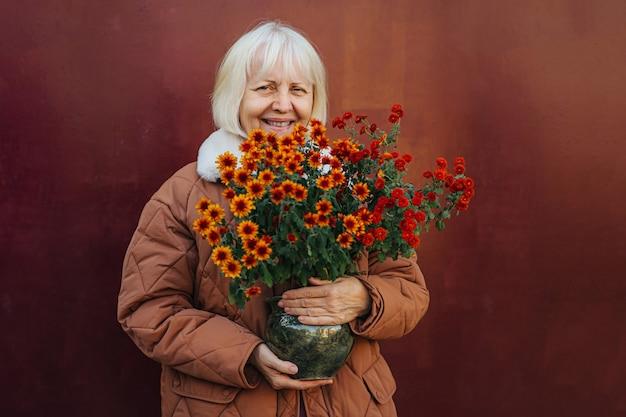 Cieszę się, że starsza kobieta w odzieży wierzchniej uśmiecha się do kamery i niesie kwiaty doniczkowe na wiosenny dzień.